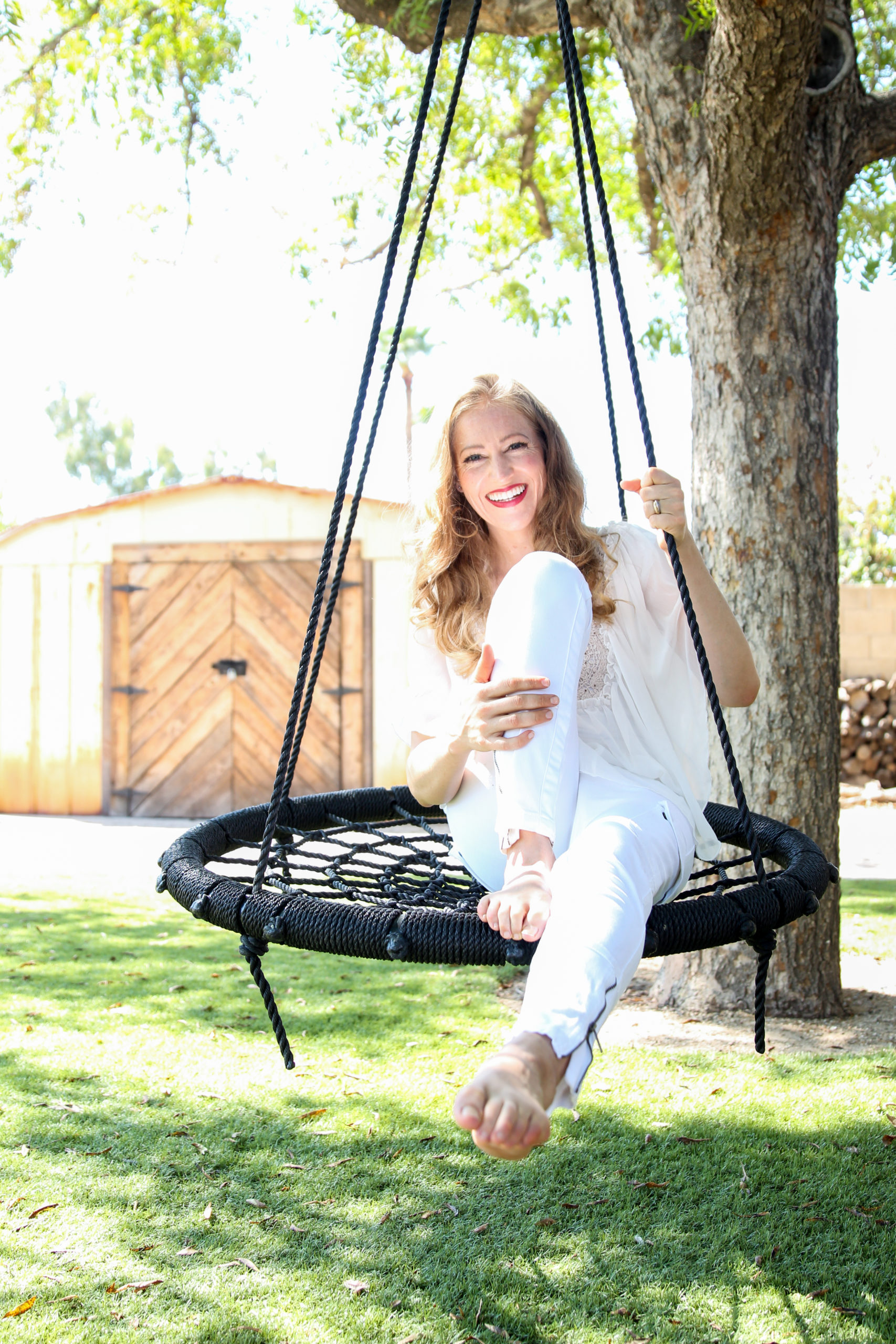 Jennifer Campbell on a swing outside under a tree