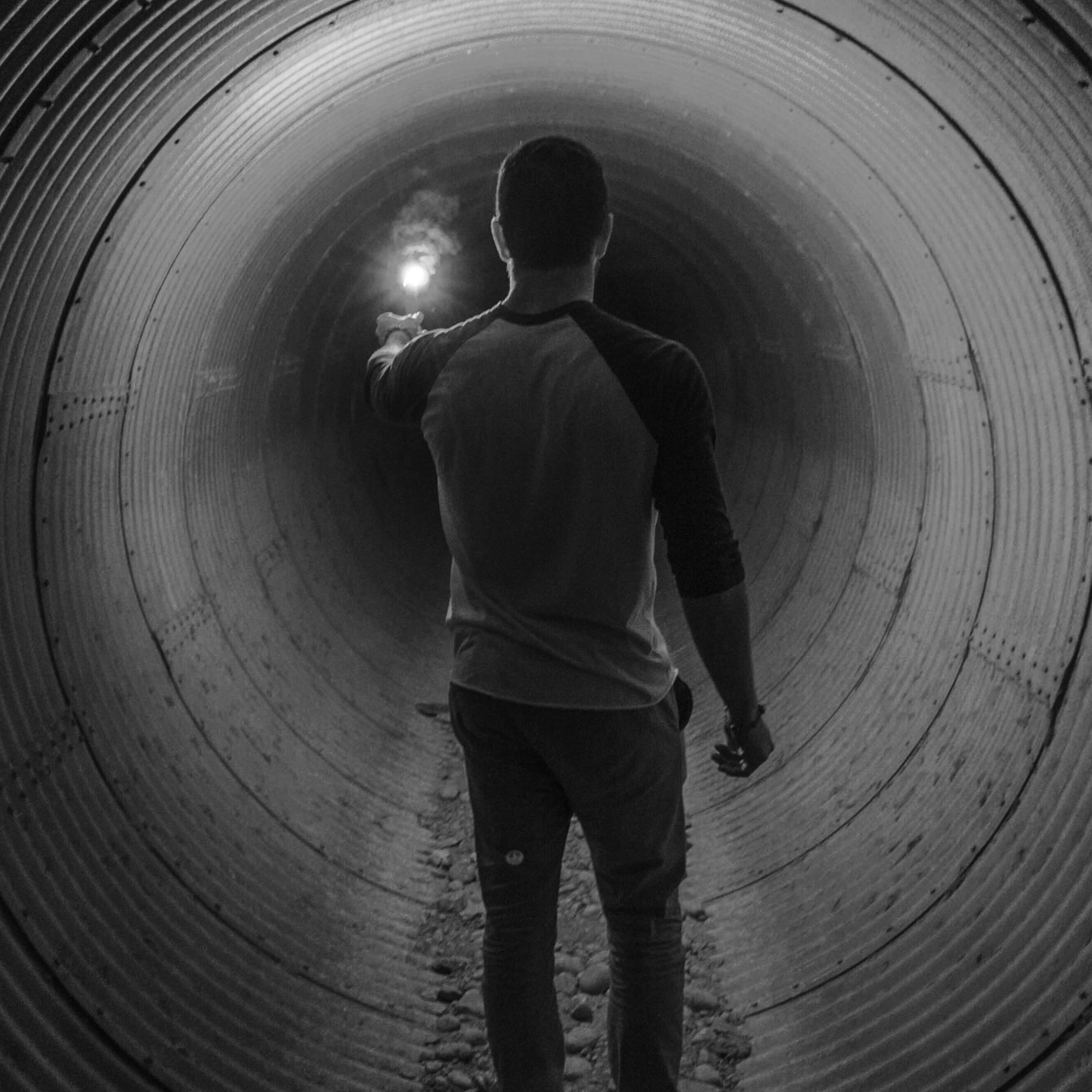 man walking through a tunnel with a match in his hand to overcome fear