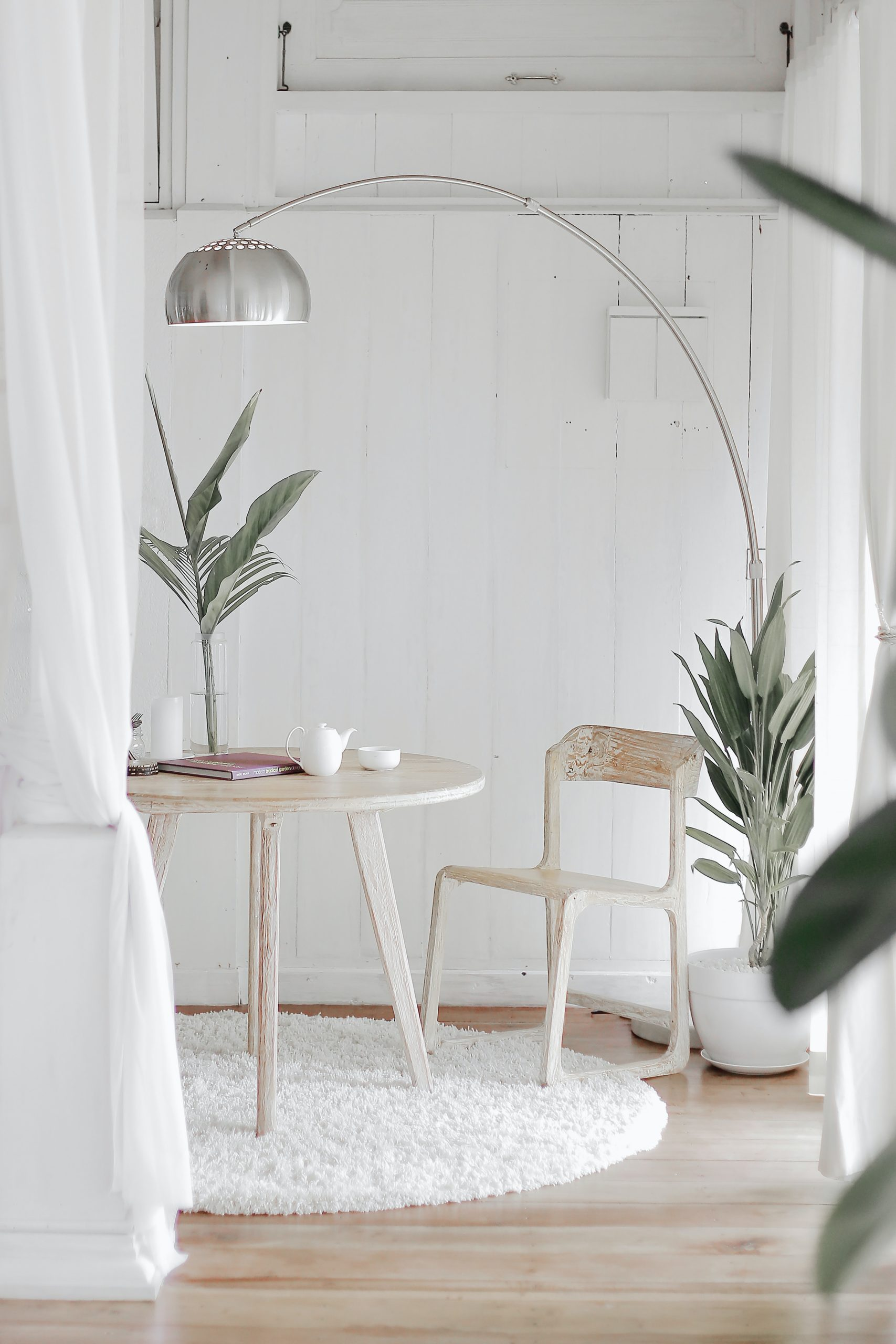 blue color code personality likes a clean white room with a table, light fixture, and plant