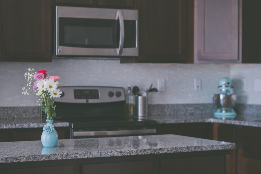 flowers sitting on a kitchen countertop with a microwave and stove in the background