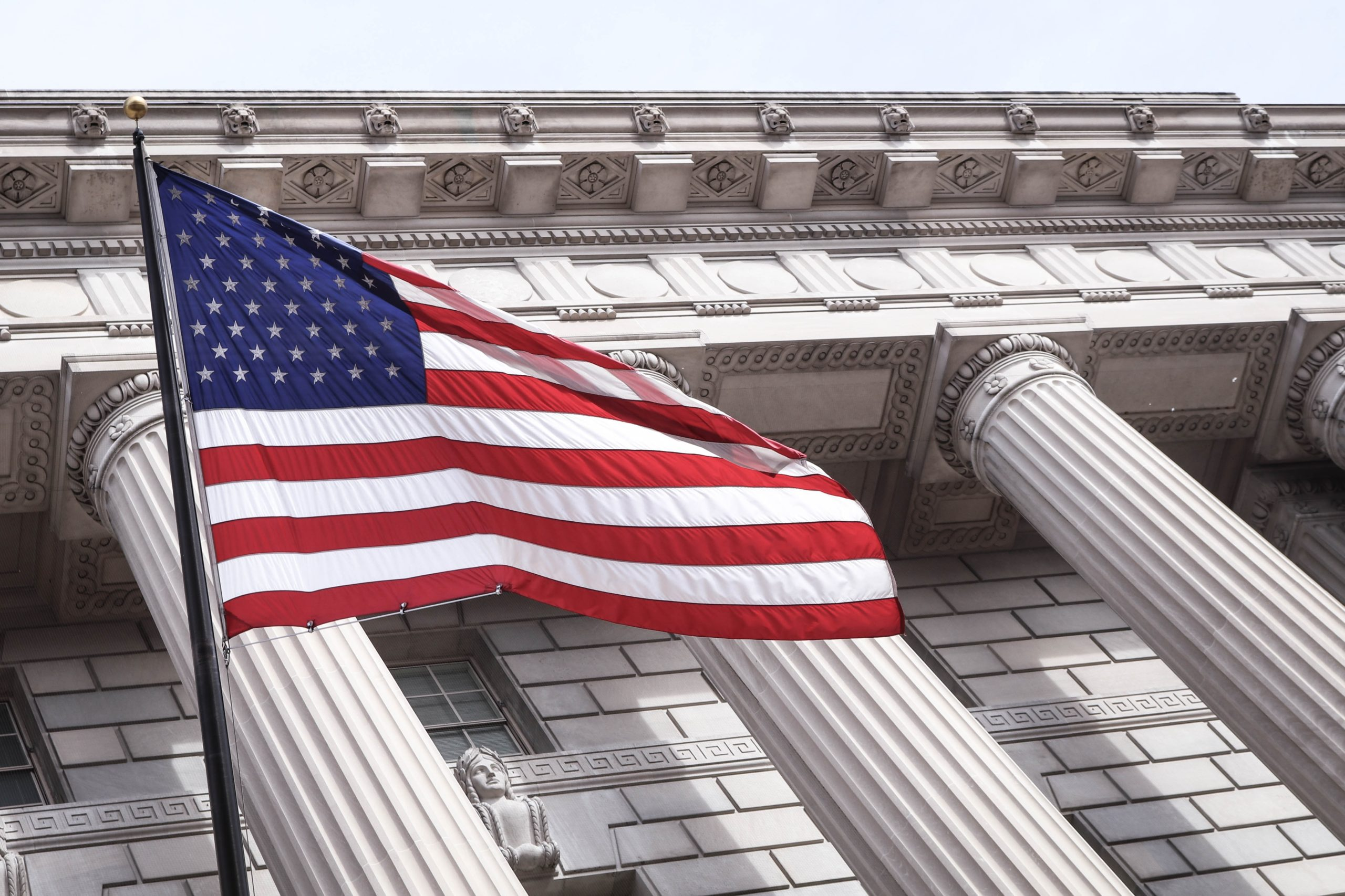 american flag waving in front of a government building