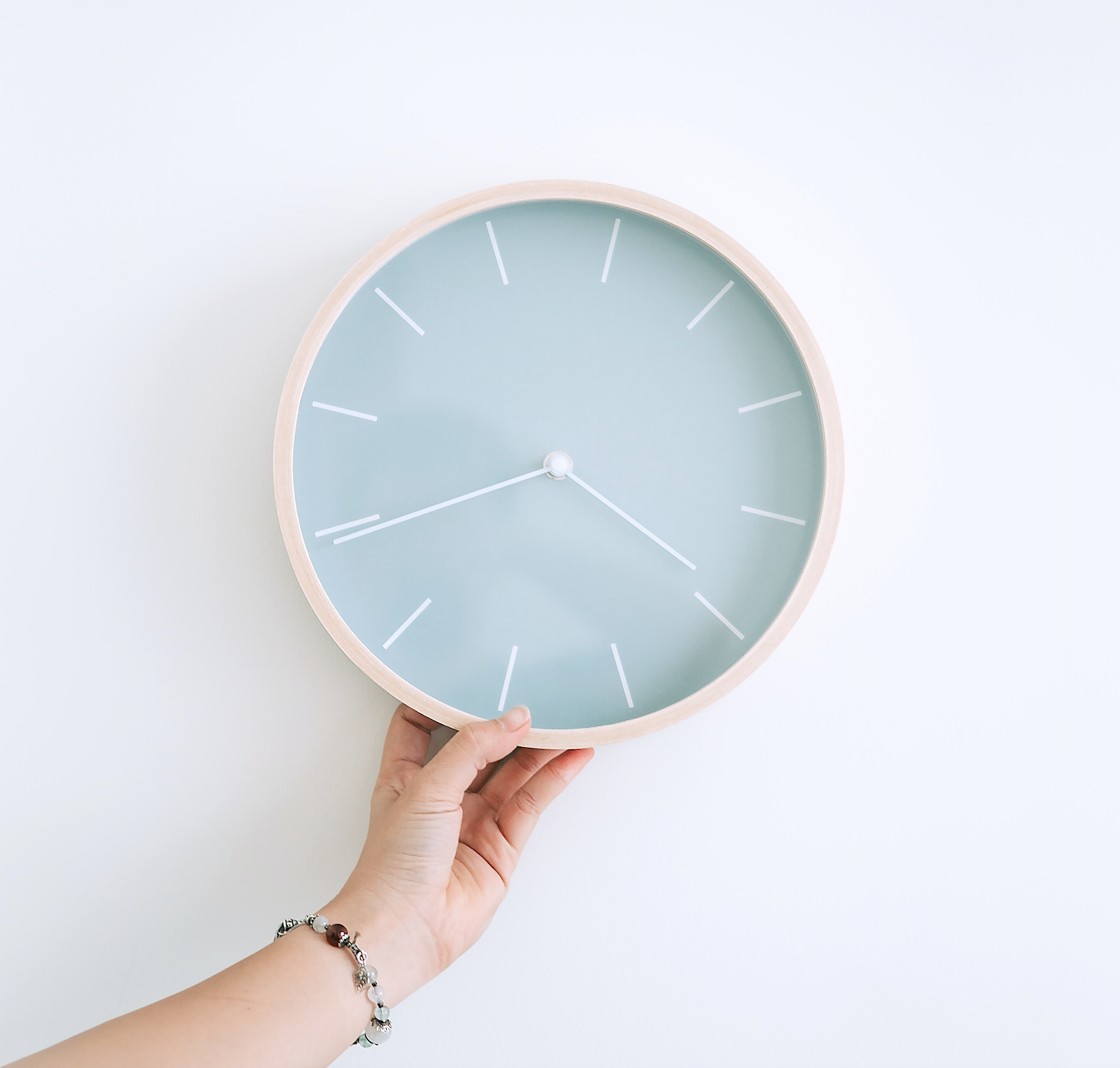 teal clock showing 20 minutes before four being held by a woman's hand
