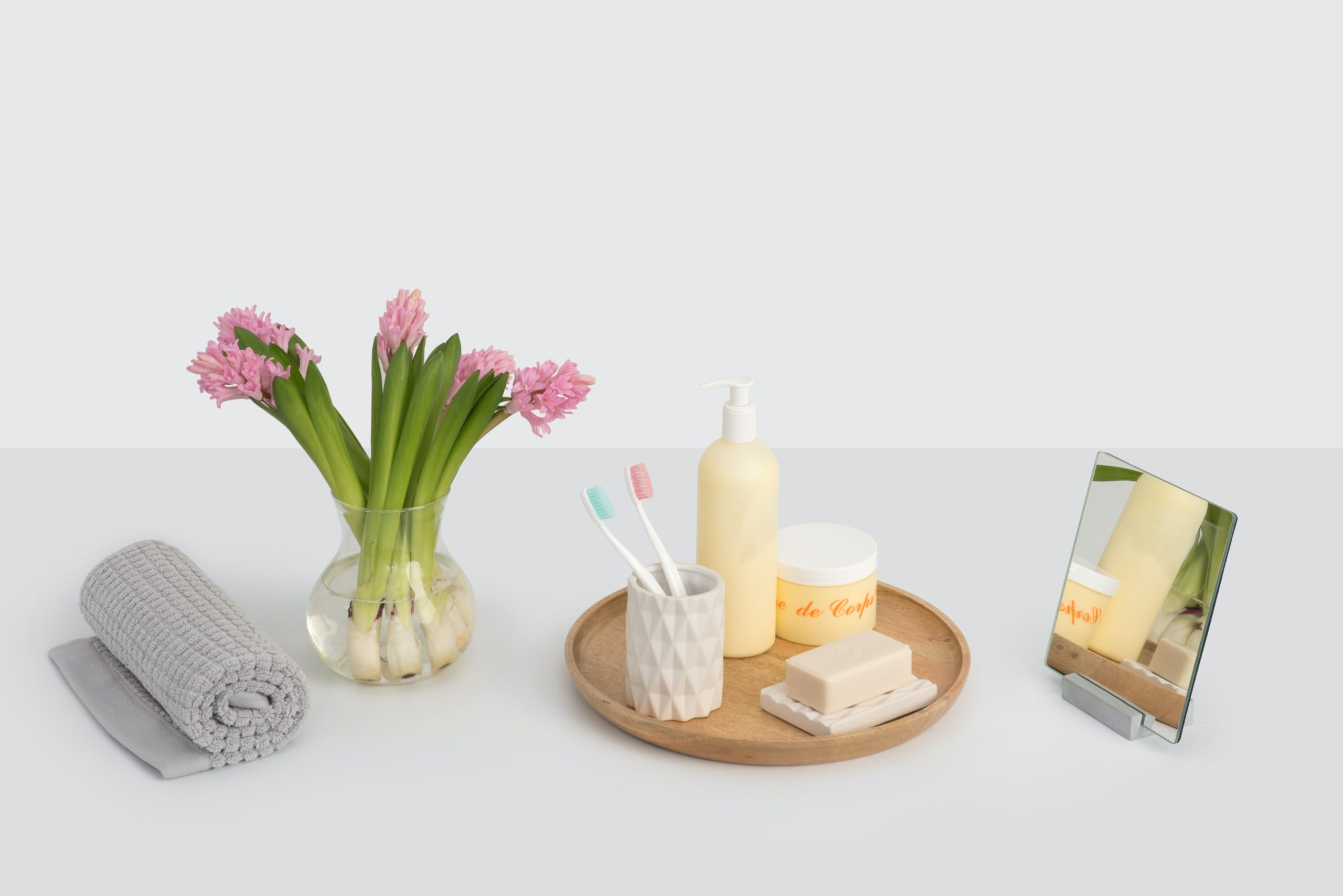 decorative bathroom display with toothbrushes and soaps with grey backdrop