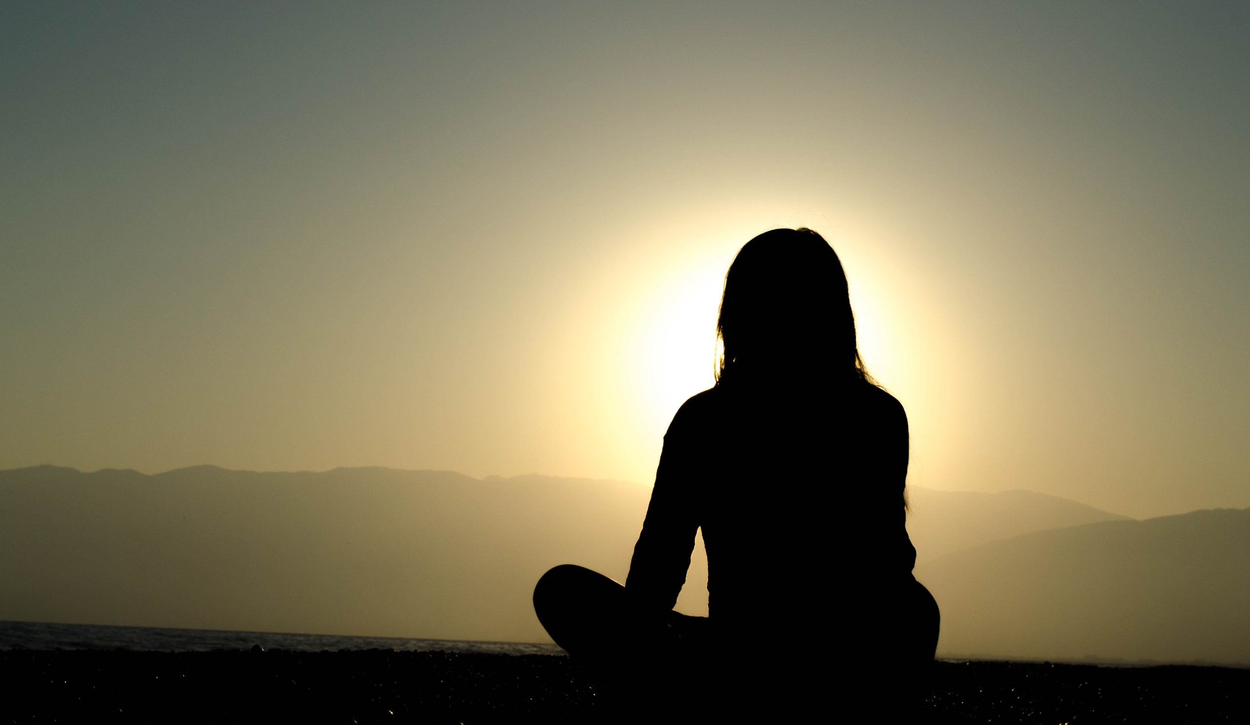 silhouette of a woman sitting cross legged with mountains in the distance with the sun shining behind her